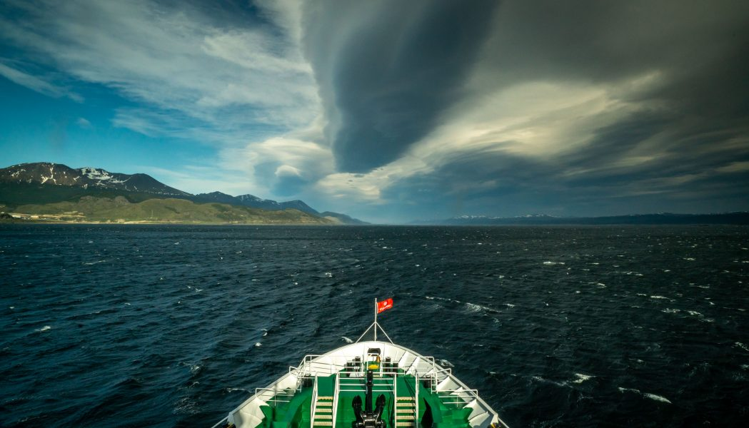 A ship setting sail into the Beagle Channel under stormy skies