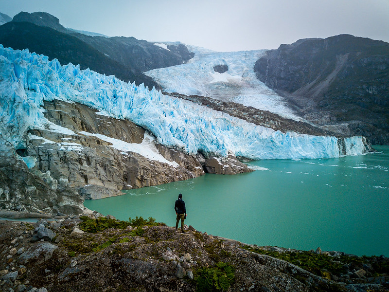 A hiker admires a sapphire-blue glacier and peppermint glacial lake