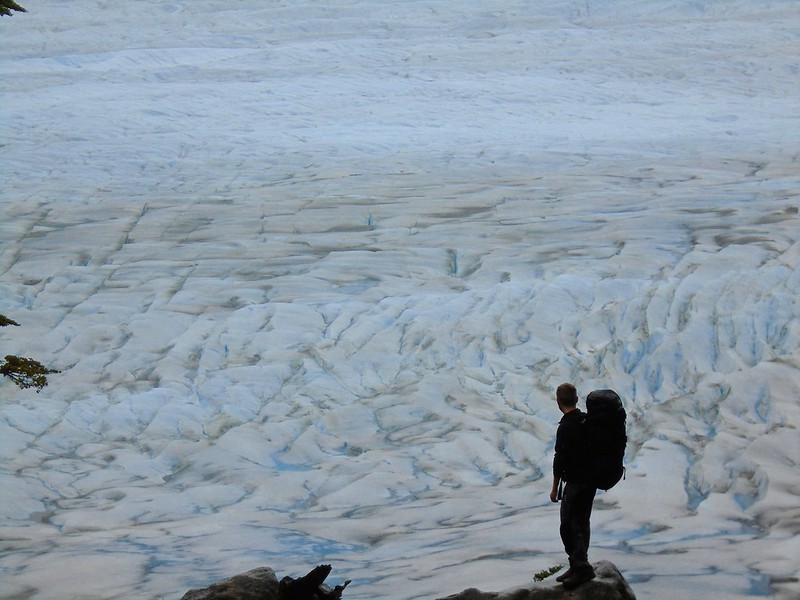 A hiker looks down on a huge glacier from above