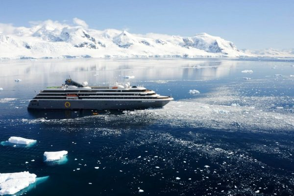 An expedition ship in Antarctica surrounded by snowy mountains and icebergs