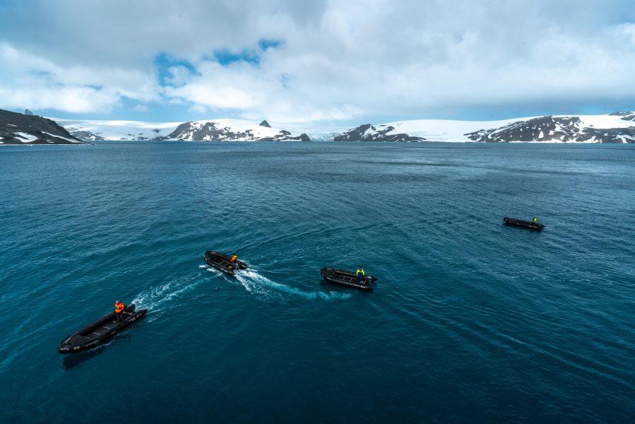 4 black rubber zodiac boats in the blue ocean in Antarctica