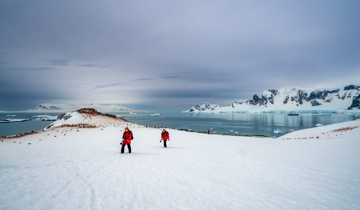 Two photographers in red jackets exploring on the Antarctic Peninsula