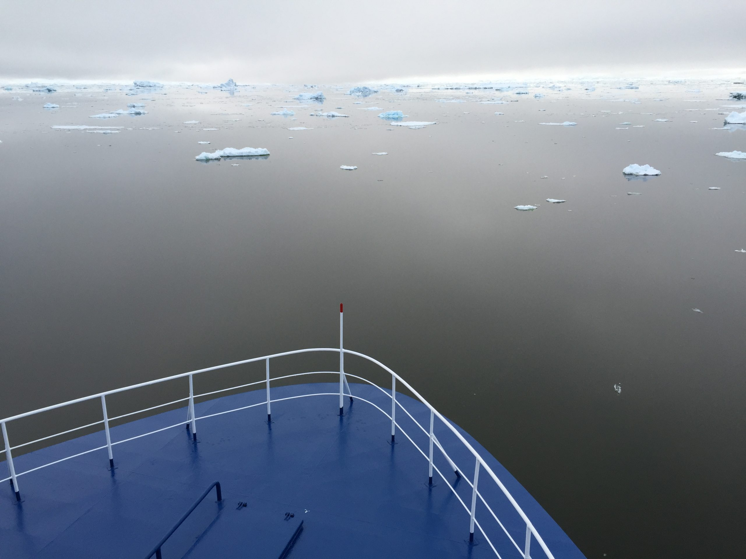 A view over the bow of a ship navigating through still icy waters in Antarctica