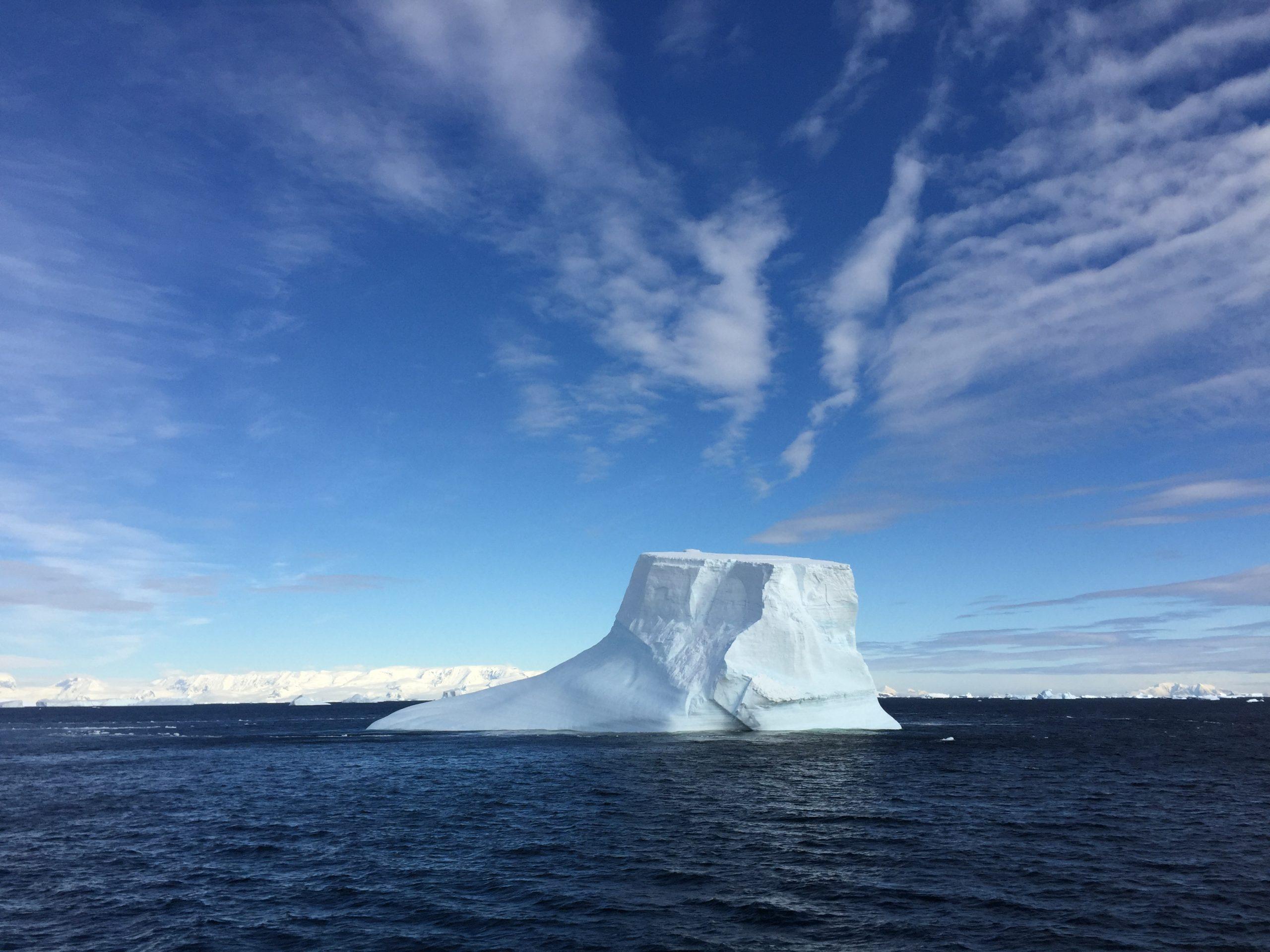 A vast iceberg floats under an expansive blue sky