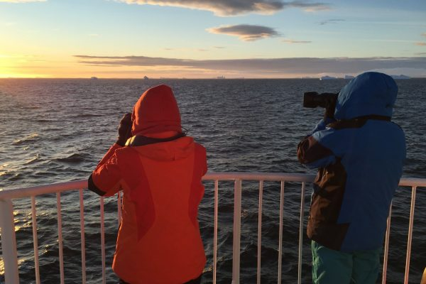 Two travellers photograph an Antarctic sunrise