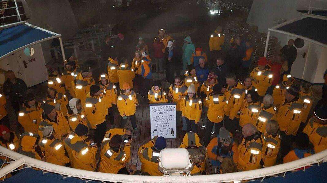 Passengers on board a ship in Antarctica celebrating crossing the Antarctic Polar Circle