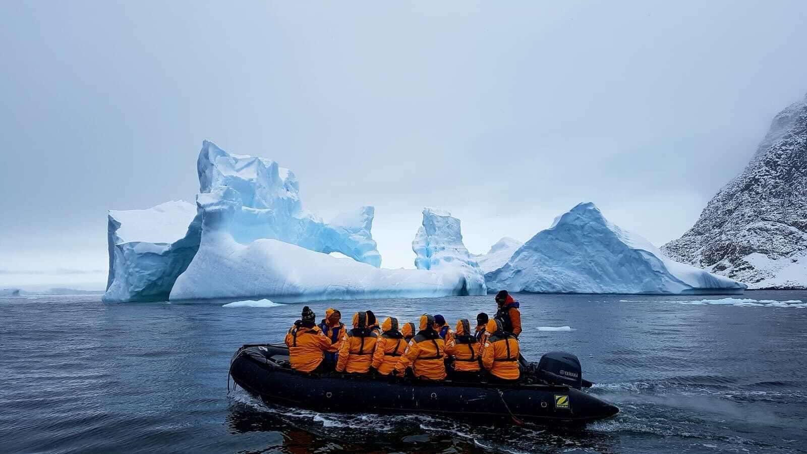 A rubber exploratory vessel full of people explores around icebergs in Antarctica