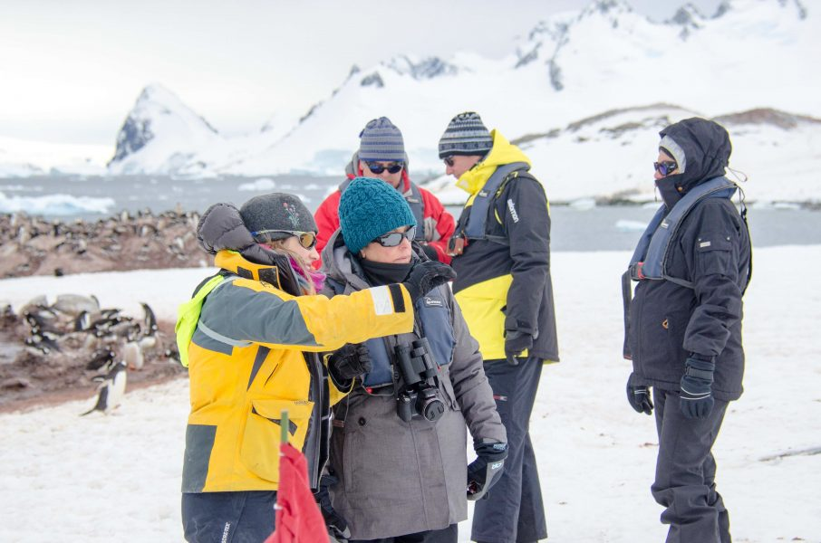 An Antarctic guide with her travellers during a landing