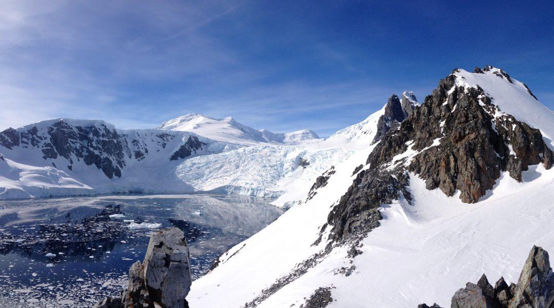 Snow-draped Orne Harbour, Antarctica, under blue skies and sunshine