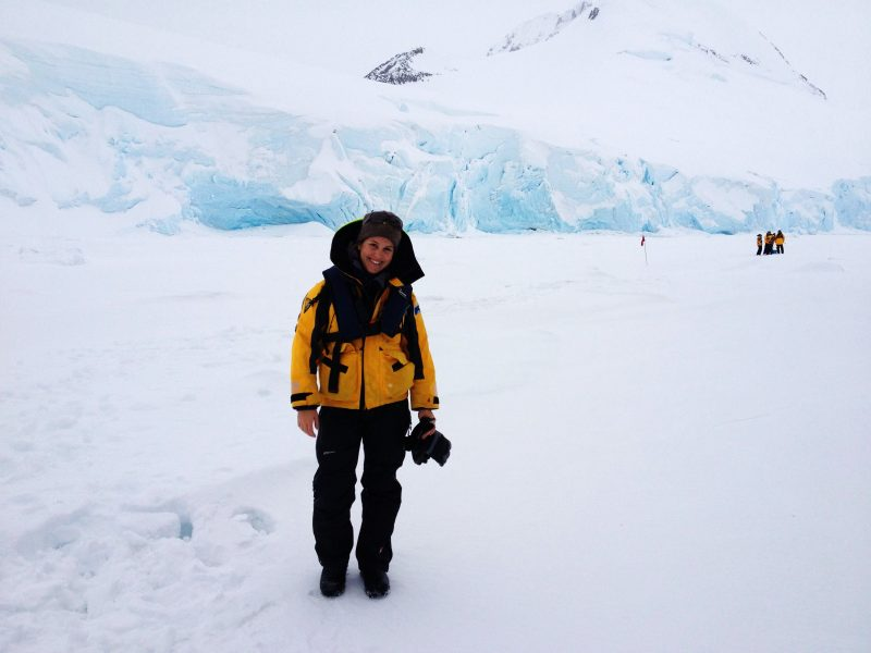 A woman in a yellow jacket in Antarctica surrounded by snow and ice