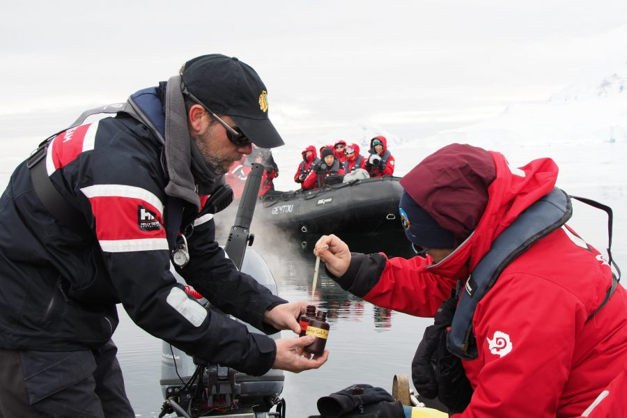 An Antarctic expedition leader assists travellers as part of a Citizen Science programme