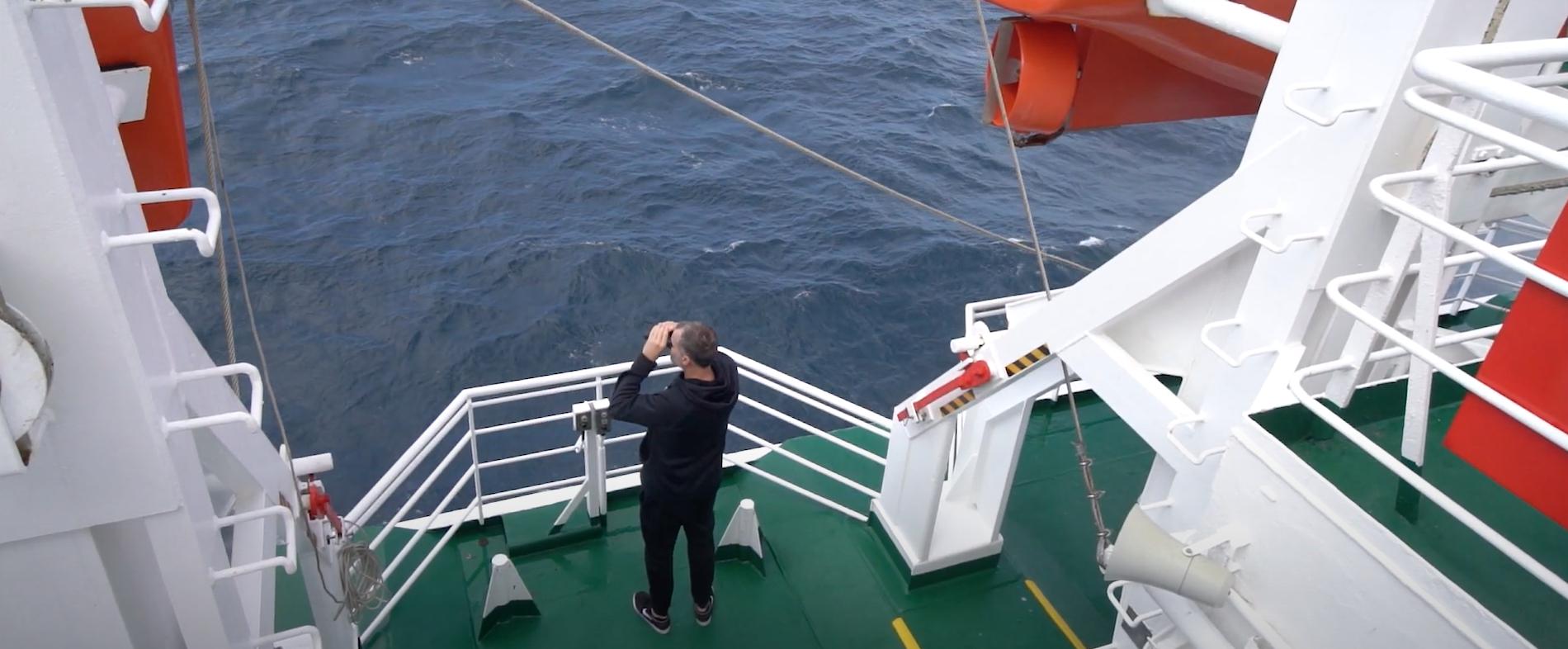 A man using binoculars to spot wildlife from an Antarctic ship