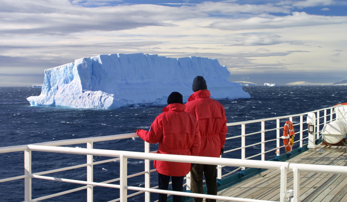 A couple in red jackets staring out at icebergs from an Antarctic cruise ship