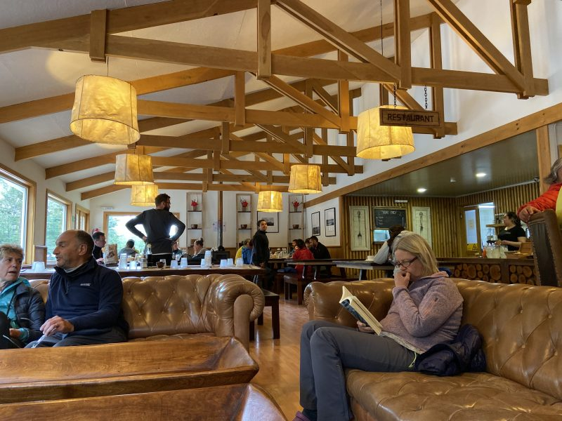 People relaxing in the restaurant of a rustic hiking hostel in Patagonia