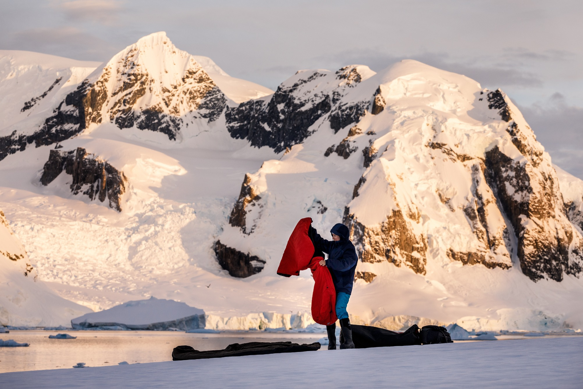 A traveller prepares a bivvy bag in Antarctica ready to sleep out on the snow