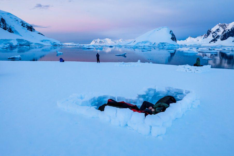 Two people in bivvy bags sleeping in Antarctica