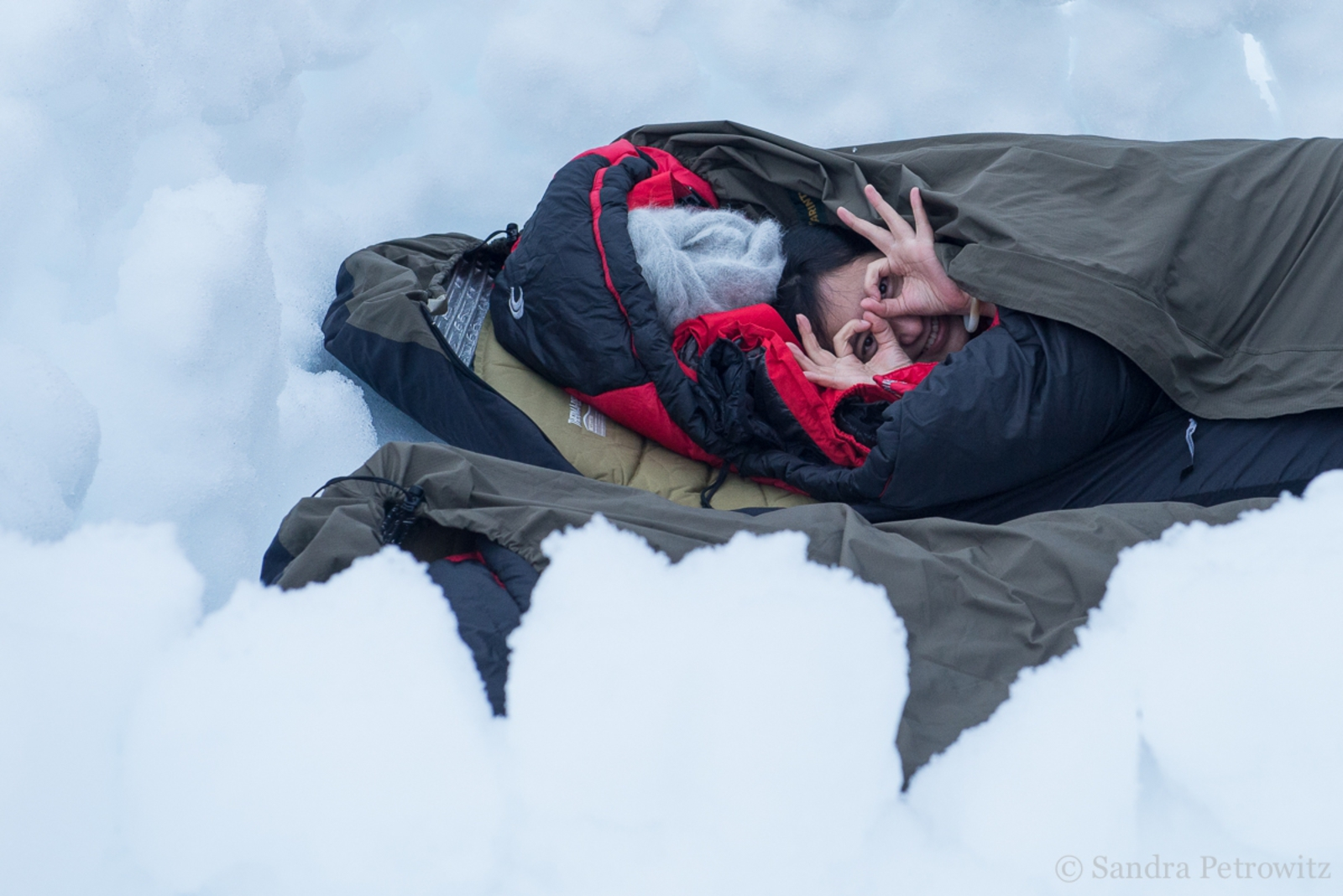 A traveller in a bivvy bag in the snow on the Antarctic Peninsula