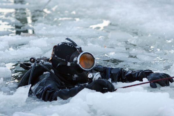 A scuba diver resurfaces in Antarctica amidst the brash ice