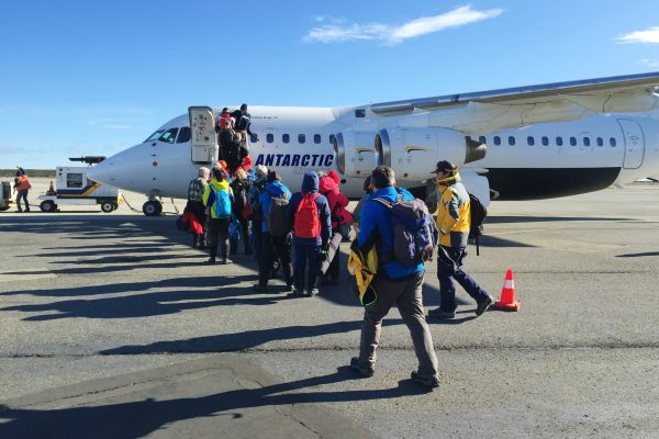 A small aircraft on the tarmac with adventure travellers boarding