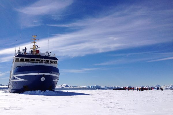 A ship moored in the ice in Antarctica with passengers exploring on the ice