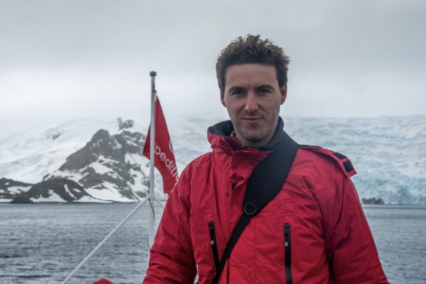 A man in a red jacket on board the deck of a ship sailing in Antarctica